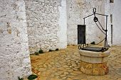 picture of water well  - view of a courtyard with an old water well - JPG