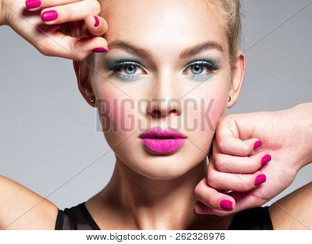 Beautiful woman face with blue makeup of eyes and pink nails ...