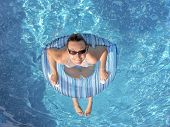 Young woman inside inflated tube wearing sunglasses posing in swimming pool