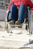 Closeup of handicapped woman practicing wheelchair riding over obstacle course for disabled