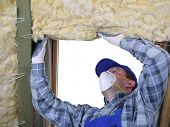 foto of rafters  - Worker thermally insulating a house attic using mineral wool - JPG