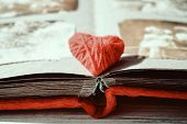 Red Thread Heart On Open Photo Album On Wooden Table Background. Vintage Book Or Photo Album With Th poster