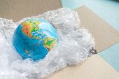Physical Globe, Earth In Plastic Wrap In Carton Box On Blue Background With Copy Space Recyclable Pa poster