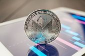 Close-up Photo Of Monero Cryptocurrency. Monero Physical Coin On The Tablet Computer. Tablet Showing poster