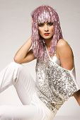 beautiful girl dressed for carnival wearing glossy pink wig and silver blouse on light background