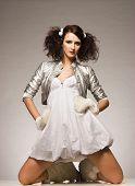 beautiful brunette winter girl wearing furry gloves and boots and white dress on light background poster