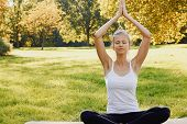 Girl Meditates While Practicing Yoga Outdoors In Park. Relaxation, Calmness, Balance And Happiness C poster
