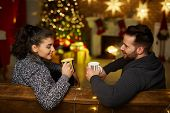Christmas couple at home in Winter. Happy young couple drinking tea at home in Christmas time. Chris poster
