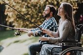 People On Wheelchairs With Fishing Rod In Park. Disabled Young Man. Woman On Wheelchair. Relaxing In poster