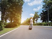 Woman Traveller Walking Alone With Luggage Along The Street At Sunny Day. Travel And Touristm Concep poster