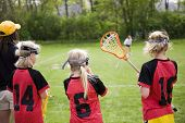 Female lacrosse players on the sideline of a game