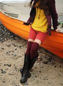 Slim woman legs gressed in a knitted stockings, sitting on a boat on an ocean beach poster