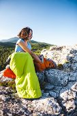 The Girl Is Packing Things In A Backpack. A Traveler Sits In A Sleeping Bag On Top Of A Mountain. A  poster