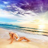 Woman sunbathing on the beach at sunrise time