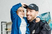 Close-up Portrait Of Smiling Young Father In Police Uniform Carrying His Little Son And Looking At C poster