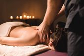 Mens Hands Make A Therapeutic Neck Massage For A Girl Lying On A Massage Couch In A Massage Spa Wit poster
