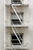 pic of brownstone  - Fire escape ladder zigzagging across the face and windows of a brownstone that - JPG