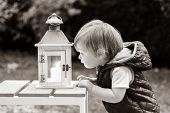 Black And White Portrait Of Little Boy Looking Curiously And Fascinated At Candle Light In Garden La poster