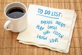 To do list - breath, dream, play, smile, laugh, listen, sign,  love. Handwriting on a napkin with a  poster