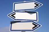 Blank three-way direction signpost with a blue sky background