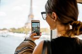 Young Woman Photographing With Smartphone Eiffel Tower From The Subway Train In Paris. Image Focused poster