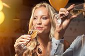 Young woman holding white wine glass and taking a sip. Closeup face of beautiful blond girl enjoying poster