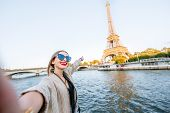 Young Woman Tourist Making Selfie Photo With Eiffel Tower On The Background From The Boat During The poster
