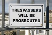 Trespassers will be prosecuted sign on a metal fence.