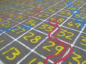 Snakes and ladders numbers game on a children's playground.