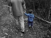 Little boy blue walking in the woods with his father, all colors but blue are desaturated