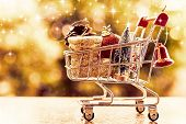 Xmas Decorative Items In Mini Shopping Cart Or Trolley Against Blurred Natural Background For Christ poster
