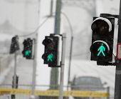 Row of green traffic lights for pedestrians, shallow focus, falling snow