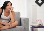 Thoughtful Young Woman Sitting On Sofa In Modern Living Room