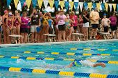 Youth Swimmer Swims Backstroke As Spectators Look On