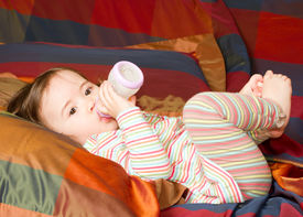 picture of polly  - pretty baby girl with infant formula in bottle on bad - JPG