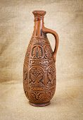 image of loamy  - Ancient brown ceramic bottle on canvas background - JPG
