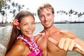 Hawaii couple happy on Hawaiian beach. Woman wearing flower lei garland and man giving shaka aloha h
