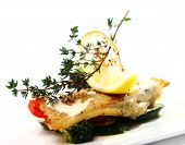 Gourmet style grilled fish with vegetables and green on a plate