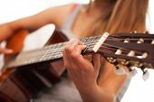 Closeup image of guitar in caucasian woman hands