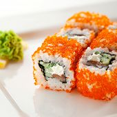 Maki Sushi with Fresh Salmon, Cucumber and Cream Cheese inside. Tobiko outside