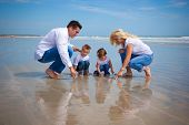 foto of family fun  - Family on a beach looking at findings in the sand - JPG