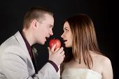Young Lovers Woman And Man Biting An Apple