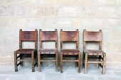 Four Vintage Chairs At The Stone Wall
