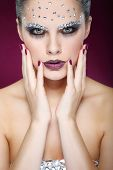 Portrait of sexual beautiful girl with strasses on face, on a violet background