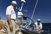 Sailors at the helm of a sailboat in sea against blue sky