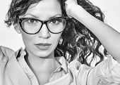 Woman wearing retro ( nerd ) glasses specs. Black and white fine art styling