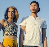 Young attractive fashionable man and woman standing and looking outward wearing stylish casual clothing