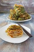 image of uncut  - A plate of sliced and stacked kimchi and a plate of wrapped and uncut kimchi - JPG