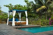 stock photo of cabana  - tropical cabana stands beside a swimming pool - JPG