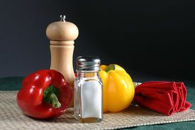 picture of salt shaker  - a small group of peppers and other objects make up a simple table setting.  - JPG